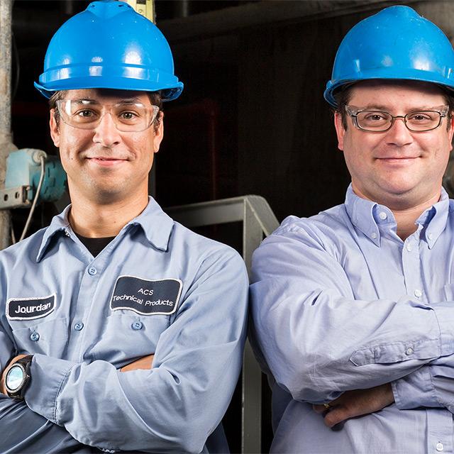 Two men wearing work helmets in ACS Tech shirts