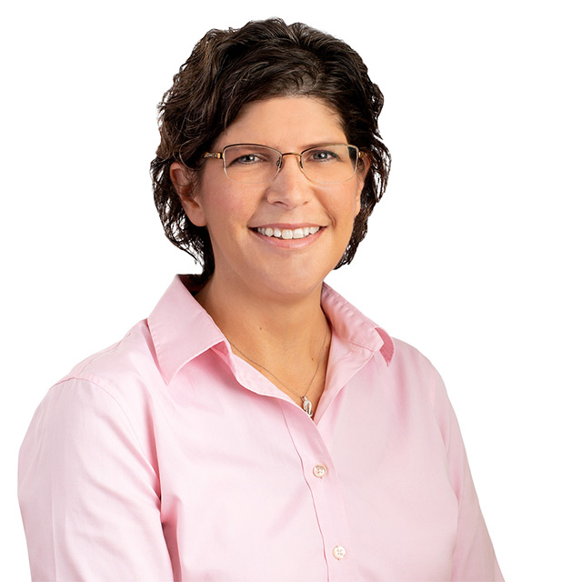 Professional headshot of female wearing pink shirt and glasses